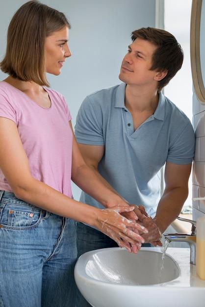Retrato de pais adoráveis lavando as mãos Foto gratuita