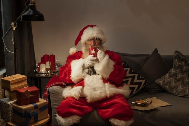 Retrato de papai noel sentado no sofá Foto gratuita
