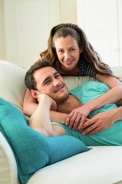 Retrato, de, par jovem, abraçar, ligado, sofá, em, sala de estar Foto Premium