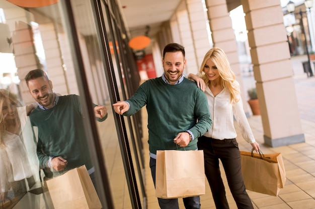 Retrato, de, par jovem, com, bolsas para compras, em, cidade Foto Premium