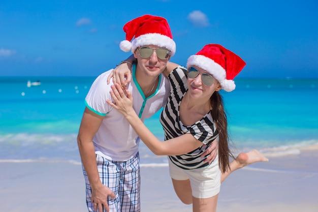 Retrato, de, par jovem, em, chapéus santa, desfrute, praia, férias Foto Premium