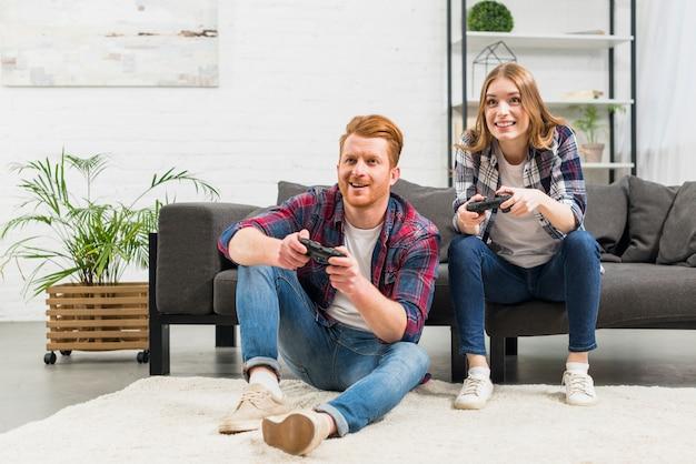 Retrato, de, par jovem, jogando videogame, junto, casa Foto gratuita