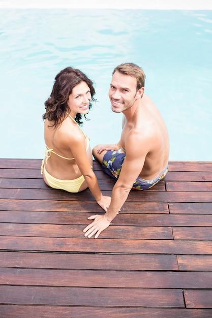 Retrato, de, par jovem, sorrindo, e, sentando, por, poolside Foto Premium