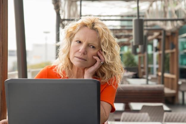Retrato, de, pensativo, mulher madura, trabalhando, em, laptop, em, café Foto gratuita