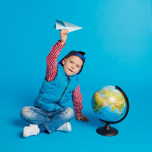 Retrato, de, pequeno, engraçado, menino, com, boné, e, brinquedo, avião papel Foto Premium