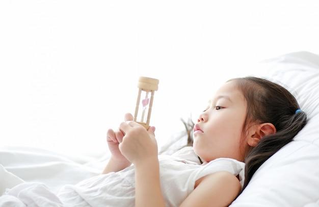 Retrato, de, pequeno, menina asiática, olhar, ampulheta, em, mão, encontrar-se cama, casa Foto Premium