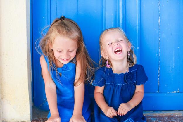 Retrato, de, pequeno, meninas sorridentes, sentando, perto, antigas, azul, porta, em, grego, vila, emporio, santorini Foto Premium