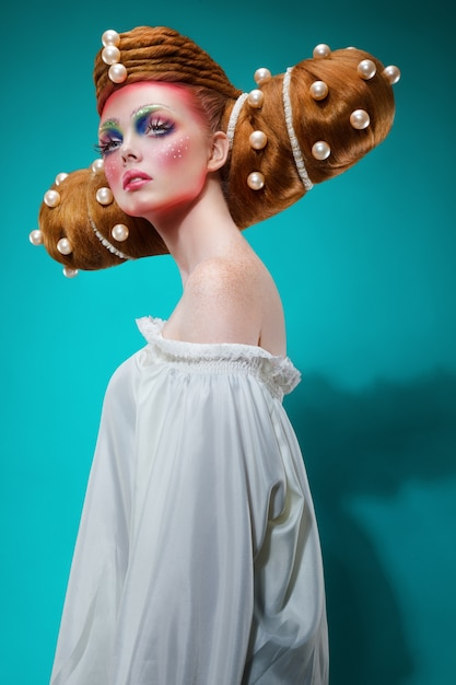 Retrato de perfil de moda de uma mulher caucasiana com uma maquiagem colorida criativa e penteado com pérolas enormes. o conceito de arte de cabeleireiro. visão vertical. Foto Premium