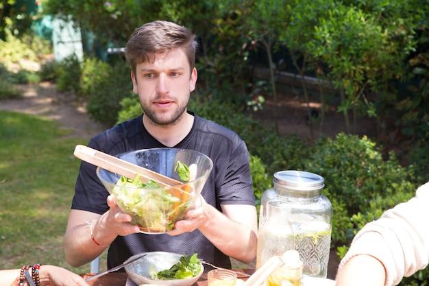 Retrato, de, sério, homem jovem, passagem, salada, em, almoço, ao ar livre Foto gratuita