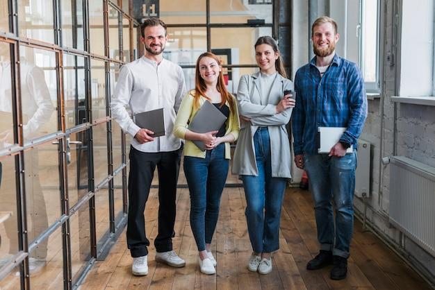 Retrato, de, sorrindo, businesspeople, ficar, em, escritório Foto gratuita