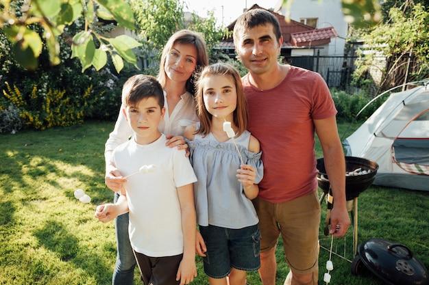 Retrato, de, sorrindo, família, segurando, marshmallow, em, piquenique Foto gratuita