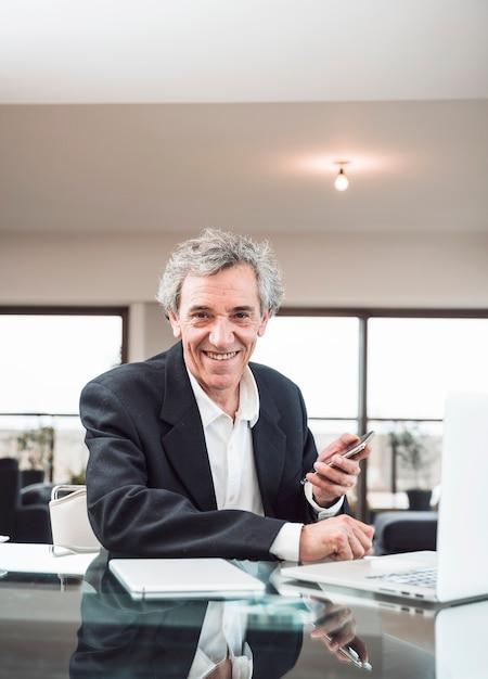 Retrato, de, sorrindo, homem sênior, com, tablete digital, e, laptop, ligado, vidro, refletivo, escrivaninha Foto gratuita