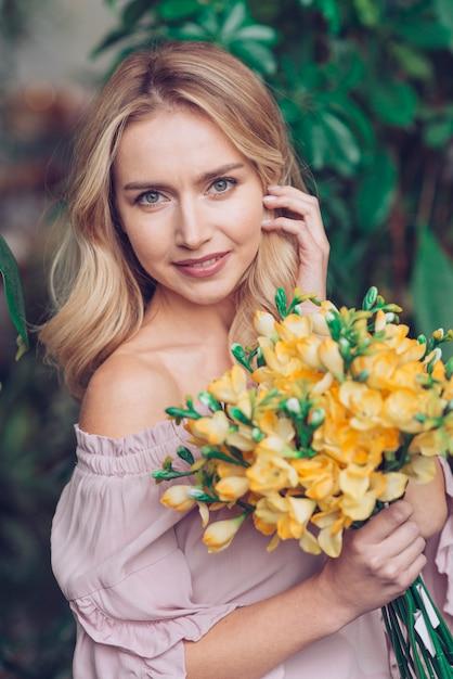 Retrato, de, sorrindo, loiro, mulher jovem, segurando, flores amarelas Foto gratuita