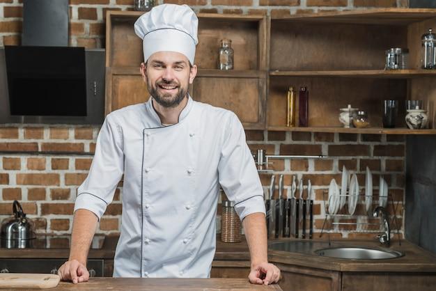 Retrato, de, sorrindo, macho, cozinheiro, ficar, cozinha Foto gratuita