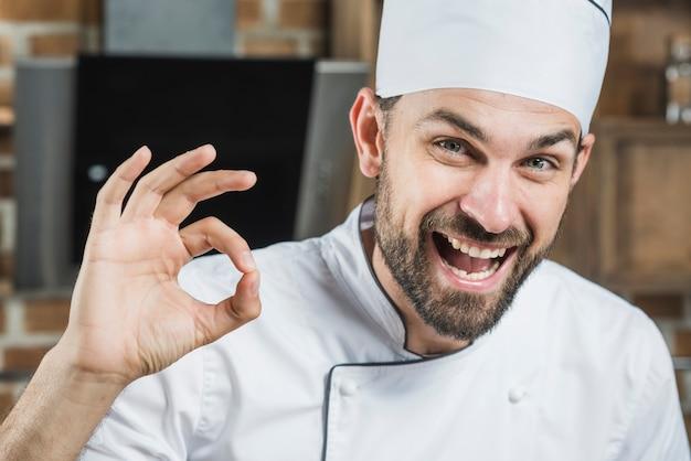 Retrato, de, sorrindo, macho, cozinheiro, mostrando, tá bom sinal Foto gratuita