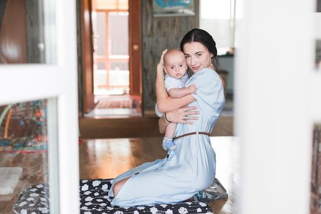 Retrato, de, sorrindo, mãe, abraçar, dela, bebê, casa Foto gratuita