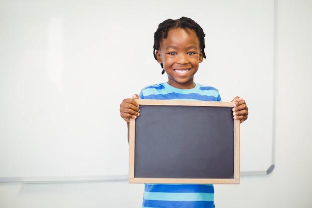 Retrato, de, sorrindo, menino escola, segurando, ardósia, em, sala aula Foto Premium