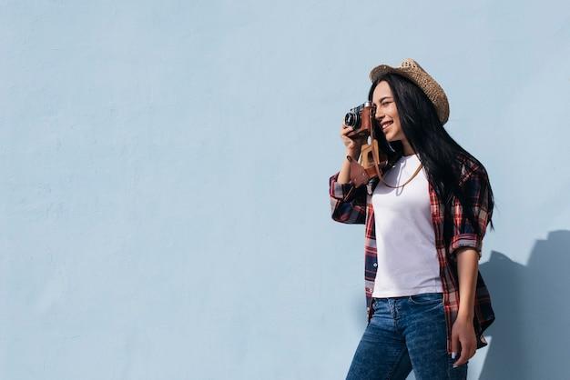 Retrato, de, sorrindo, mulher jovem, fazendo exame retrato, com, câmera, ficar, perto, parede azul Foto gratuita