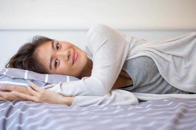 Retrato, de, sorrindo, mulher jovem, mentindo cama Foto gratuita