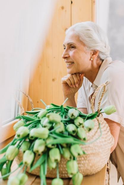Retrato, de, sorrindo, mulher sênior, com, cesta, de, tulips Foto gratuita