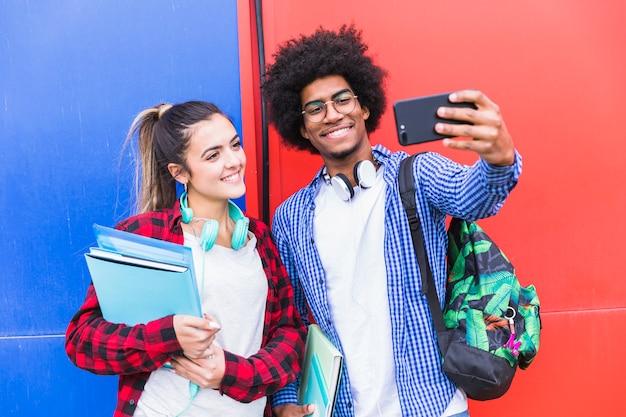 Retrato, de, sorrindo, par adolescente, levando, selfie, junto, ligado, cellphone, contra, parede colorida Foto gratuita
