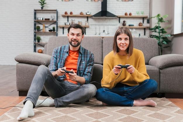 Retrato, de, sorrindo, par jovem, sentar chão, jogando videogame Foto gratuita