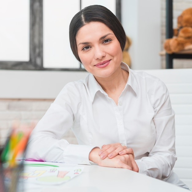 Retrato, de, sorrindo, profissional, femininas, psicólogo, sentando, em, dela, escritório Foto gratuita