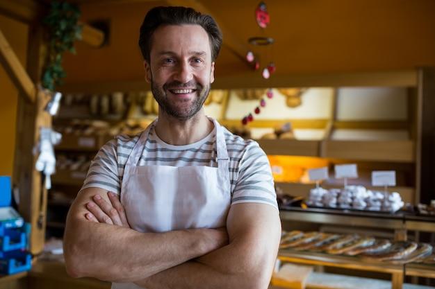 Retrato de sorrindo proprietário pé na padaria Foto gratuita