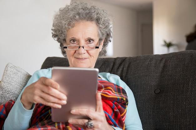 Retrato, de, sorrindo, senhora velha, usando, tablete digital, em, sala de estar Foto gratuita