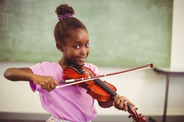 Retrato de sorrir colegial tocando violino na sala de aula Foto Premium
