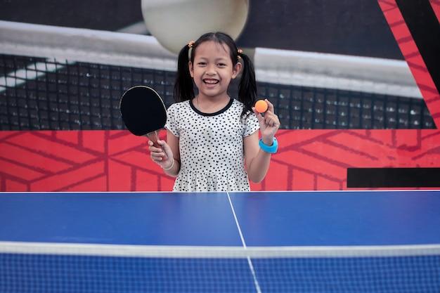 Retrato de sorriso menina asiática jogar ténis de mesa Foto Premium