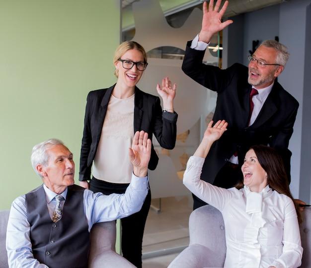 Retrato, de, sucedido, grupo negócio, waving, mãos, em, escritório Foto gratuita
