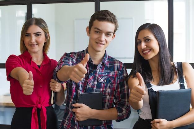 Retrato, de, sucedido, jovem, estudantes, mostrando, polegares cima Foto gratuita
