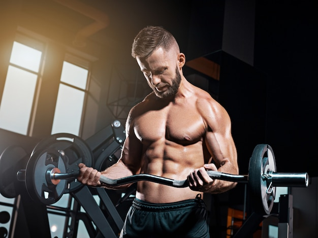Retrato de super apto muscular jovem malhando na academia com barra Foto gratuita