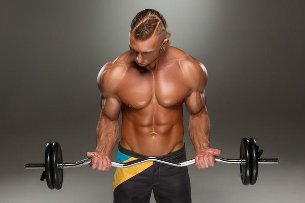 Retrato de super apto muscular jovem malhando na academia. Foto gratuita