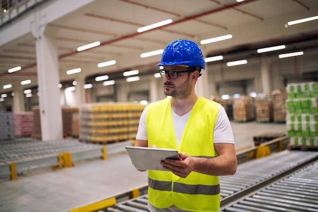 Retrato de trabalhador de armazém com tablet em pé no departamento de armazenamento Foto gratuita