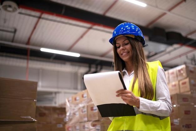 Retrato de trabalhador de armazém feminino verificando mercadorias e pacotes no departamento de armazenamento. Foto Premium