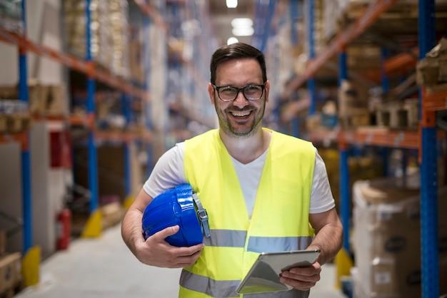Retrato de trabalhador de armazém sorridente com tablet em pé no departamento de armazenamento Foto gratuita