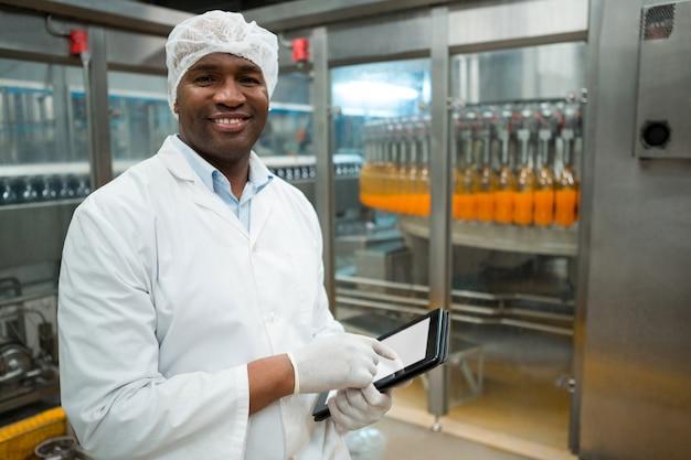 Retrato de trabalhador do sexo masculino segurando tablet digital na fábrica Foto gratuita