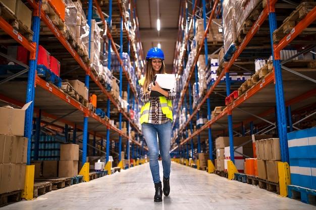 Retrato de trabalhadora confiante caminhando pelo armazém de distribuição Foto gratuita
