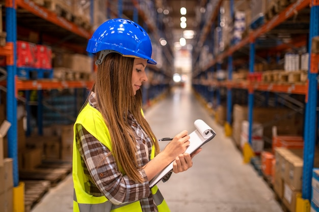 Retrato de trabalhadora em armazém de distribuição fazendo anotações Foto gratuita