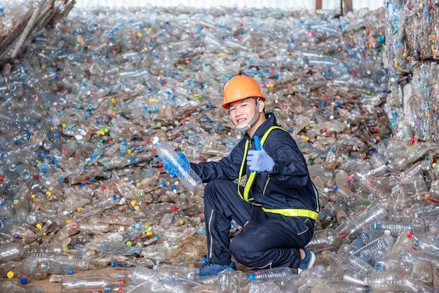 Retrato de trabalhadores de engenheiro industrial asiáticos com uma pilha de garrafas de plástico na fábrica Foto Premium