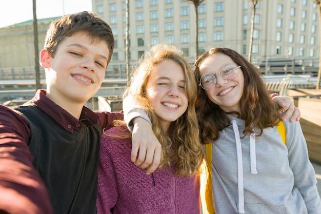 Retrato de três amigos adolescentes menino e duas meninas sorrindo e tomando uma selfie ao ar livre. Foto Premium