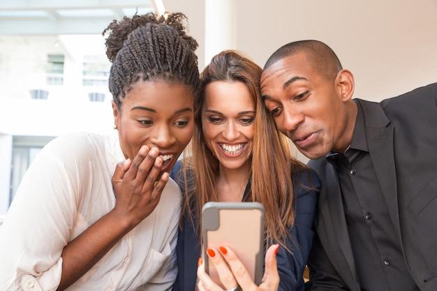 Retrato, de, três, feliz, pessoas negócio, rir, de, móvel, vídeo Foto gratuita
