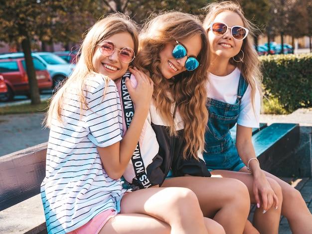 Retrato de três jovens bonitas garotas hipster sorridente em roupas da moda no verão. mulheres despreocupadas sexy, posando na rua. modelos positivos, se divertindo em óculos de sol. Foto gratuita
