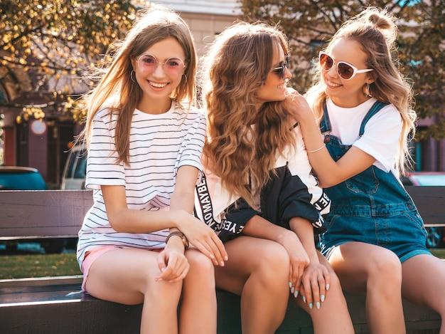 Retrato de três jovens bonitas garotas hipster sorridente em roupas da moda no verão. mulheres despreocupadas sexy, sentado no banco da rua. modelos positivos se divertindo em óculos de sol Foto gratuita