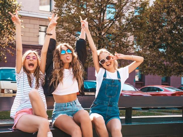 Retrato de três jovens bonitas hipster garotas sorridentes em roupas da moda no verão. mulheres despreocupadas sexy, sentado no banco na rua. modelos positivos se divertindo em óculos de sol. Foto gratuita