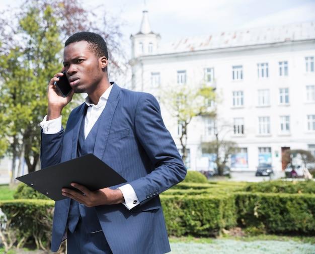 Retrato, de, um, africano, jovem, executiva, segurando clipboard, falando telefone móvel Foto gratuita