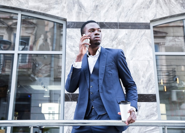 Retrato, de, um, africano, jovem, homem negócios, segurando, copo descartável, xícara café, falar telefone móvel Foto gratuita