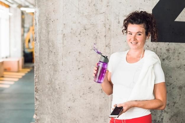 Retrato, de, um, ajuste, mulher, com, smartphone, e, garrafa água Foto gratuita
